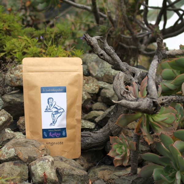 Eine mittlere Packung Kakao mit Maca & Banane ungesüßt, steht in einer von wilder Hauswurz und Eisenkraut bewachsenen Geröllhalde in den Bergen von Gran Canaria.